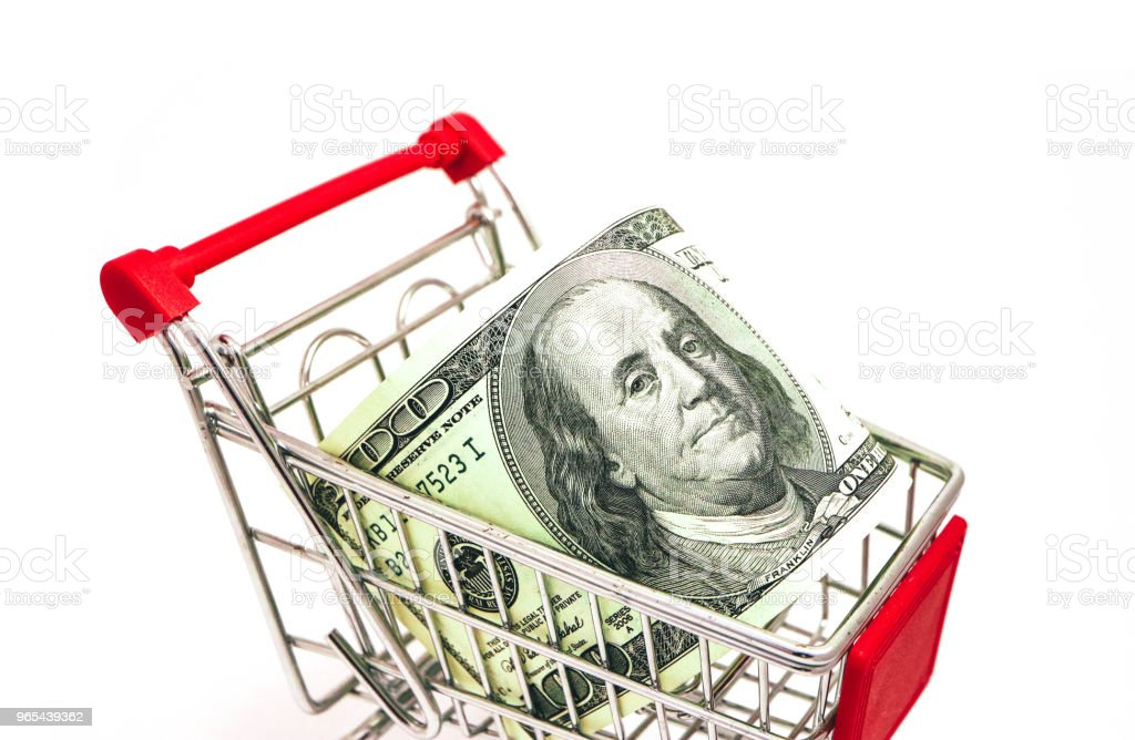 Metal basket with an American 100 dollar banknote in it. Consumption, shopping concept, pushcart. zbiór zdjęć royalty-free