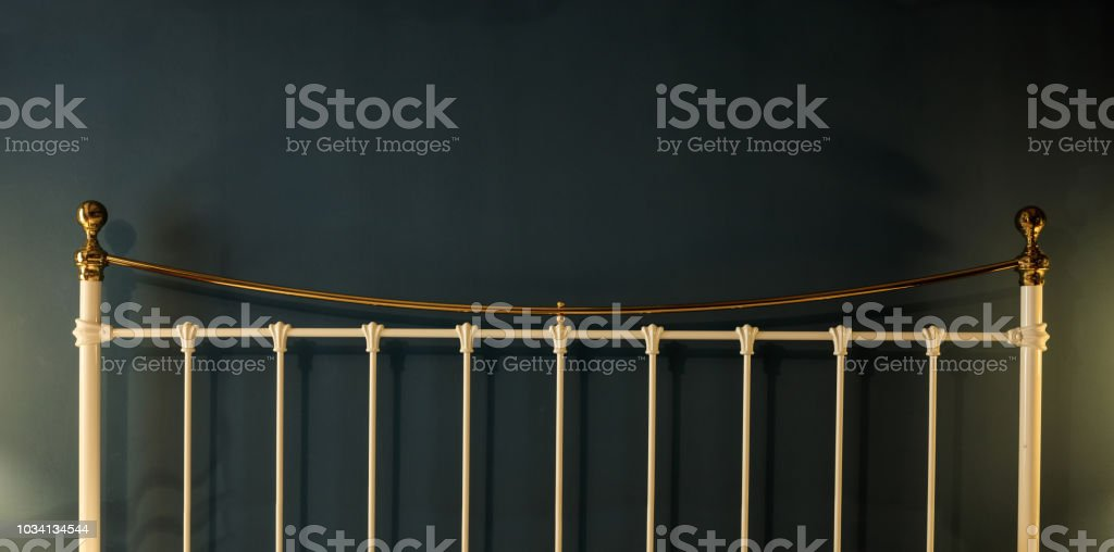 Metal bed headboard detail on black wall background, copy space