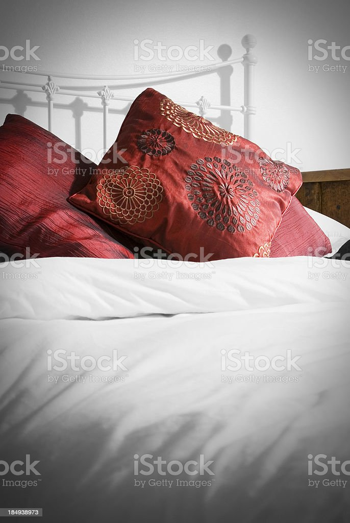 Metal bedstead bed with white duvet and red cushions royalty-free stock photo