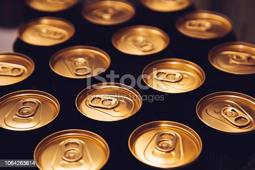 istock metal beer cans background black gold row 1064263614