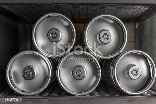istock Metal beer kegs lie in a row 1130377911