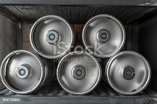 istock Metal beer kegs lie in a row 849730604
