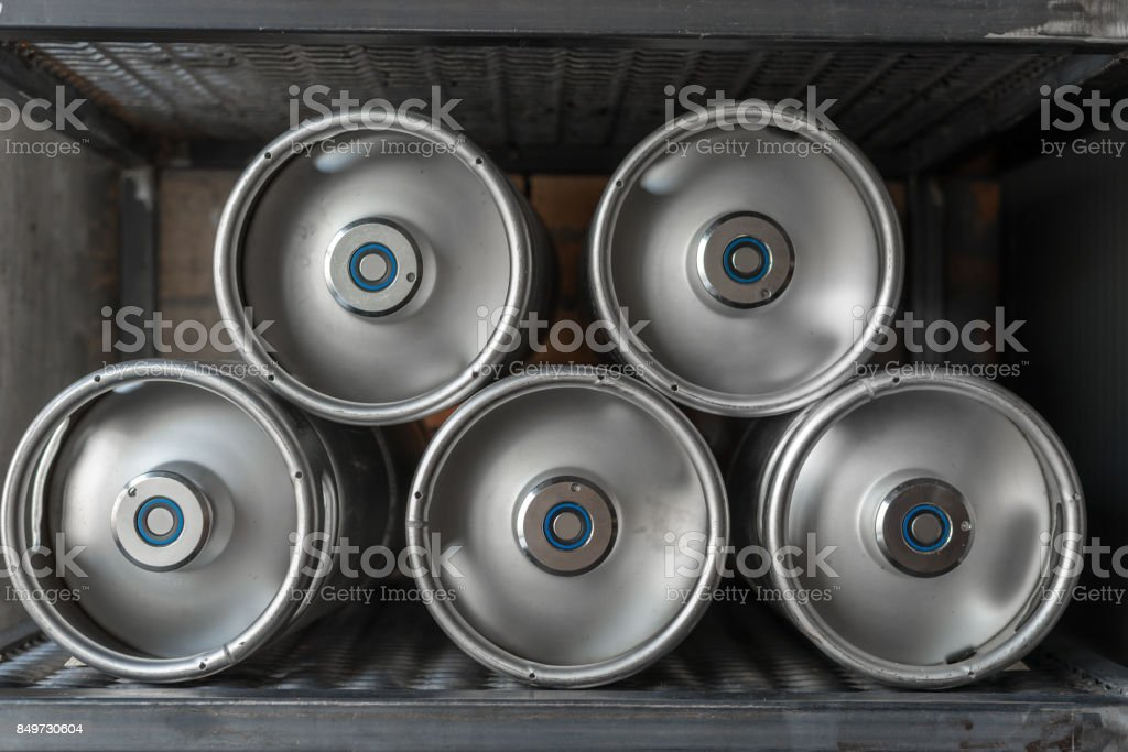 Metal beer kegs lie in a row stock photo