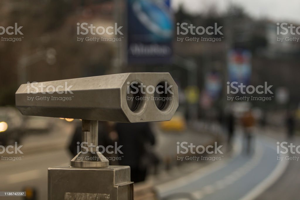Metal binoculars for public use with blurred bicycle lane in the background in Istanbul. stock photo