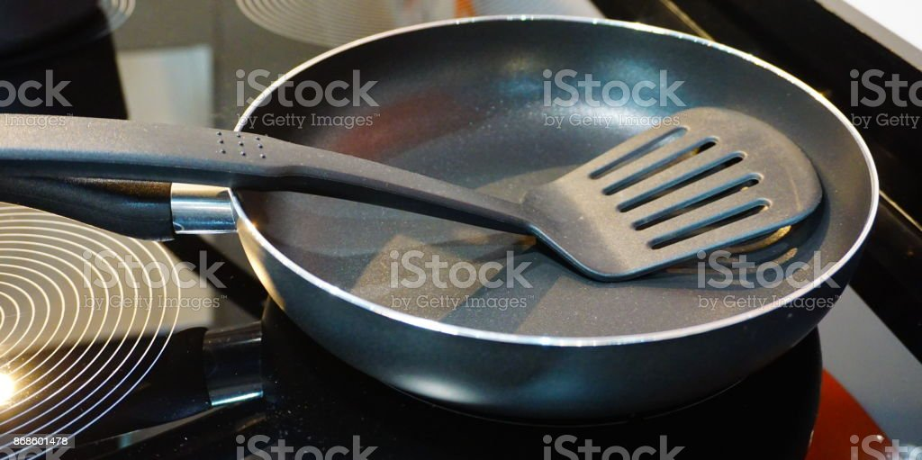 Metal black frying pan with a non-stick coating on electric stove stock photo