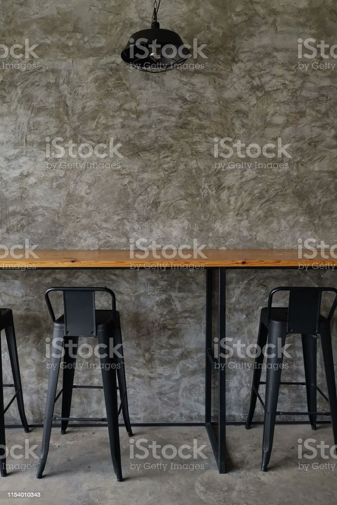 Metal black high chair with wooden table and concrete style wall in...