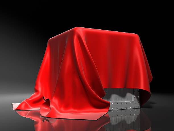 Metal box draped with red cloth, isolated on gray stock photo
