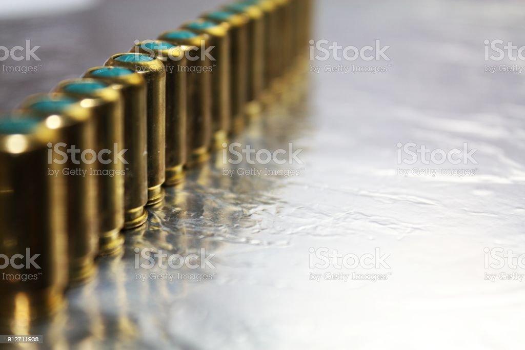 Metal brass gun hubs munitions on shiny silver desk stock photo