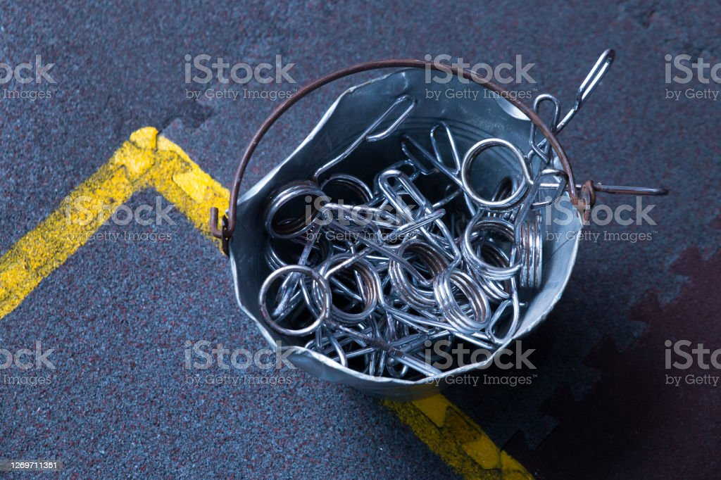 metal bucket full of spring barbell end clamps lock on a gym floor with copy space metal bucket full of spring barbell end clamps lock on a gym floor with copy space Activity Stock Photo
