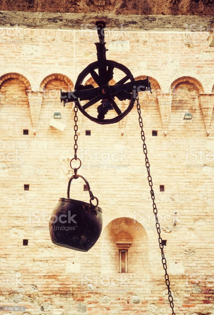 Metal bucket on a pulley hanging in the courtyard, photo filter stock photo