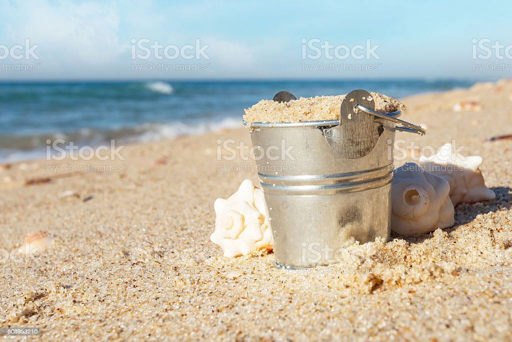 metal Bucket with sand at the beach stock photo
