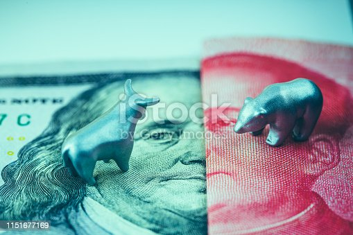 metal bull and bear on top of 100 US dollar and Chinese Yuan
