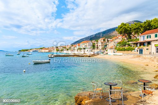 istock Metal cafe chairs on beach in Bol port with typical town architecture, Brac island, Croatia 900206852