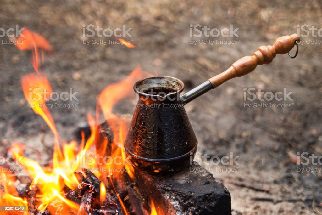 Metal cezve with hot flavored coffee on a bonfire closeup. stock photo