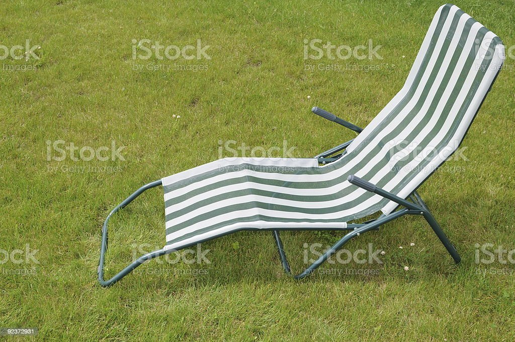 metal chair standing in a green lawn royalty-free stock photo