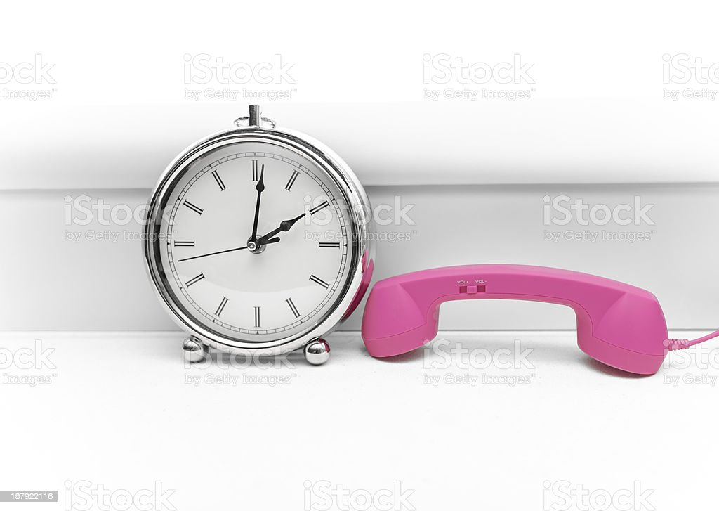 metal chrome old style alarm clock and pink duo handset stock photo
