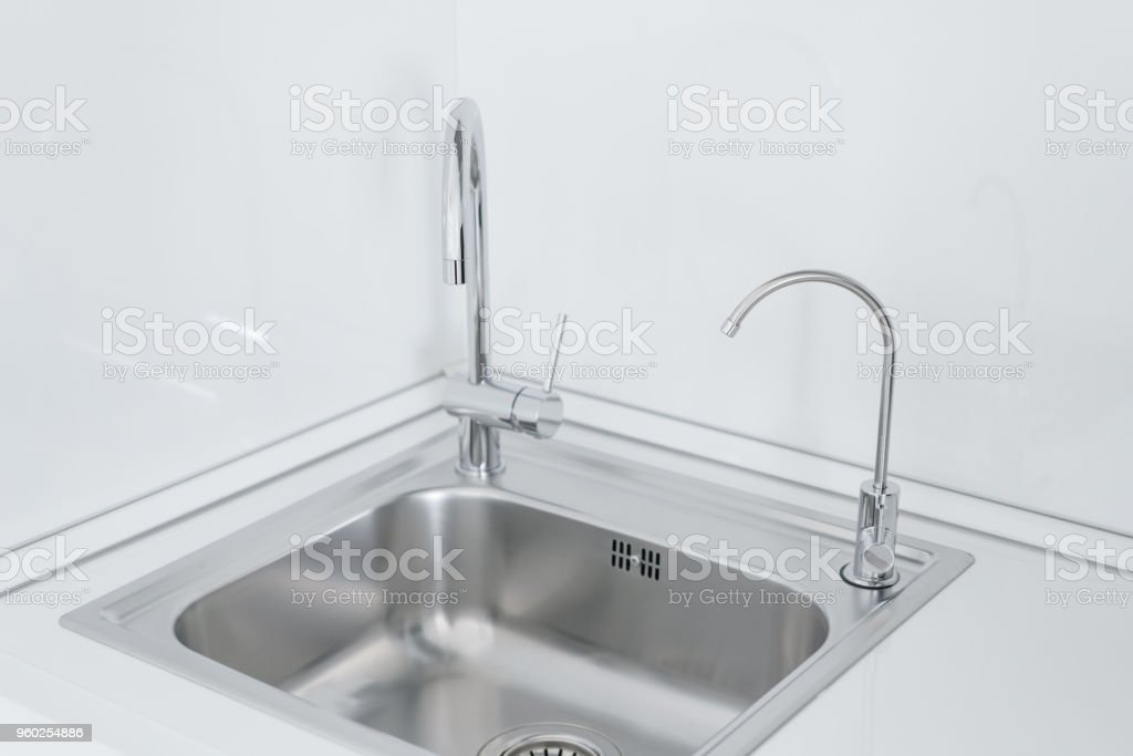 Metal chrome sink with two taps, plain and filtered water. Fragment...