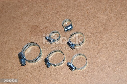 Metal clamps for hose connection isolated on wood background
