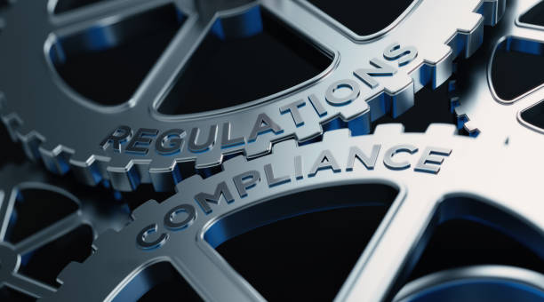 Metal Cogs With Regulations And Compliance Text - Compliance Concept Metal cogs are turning. Regulations and compliance words are written on the cogs. Horizontal composition with copy space. anonymous stock pictures, royalty-free photos & images