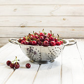 Metal colander full of freshly cherries over a rustic board. Square image.