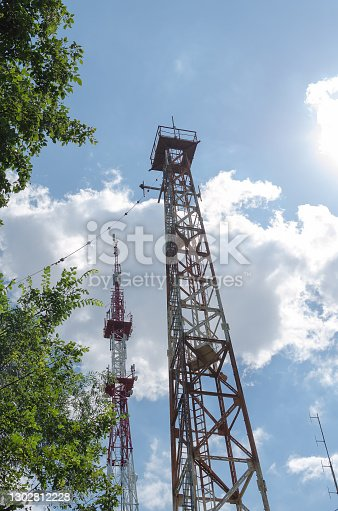 metal structure of a telecommunication tower against the blue sky .Bottom view.