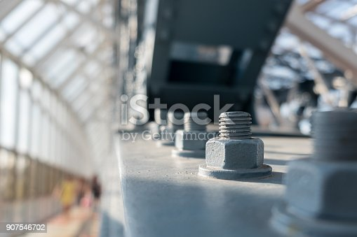 istock Metal Construction Of Modern Pedestrian Footbridge. Detail With Screws. Selective Focus. Abstract Background. 907546702