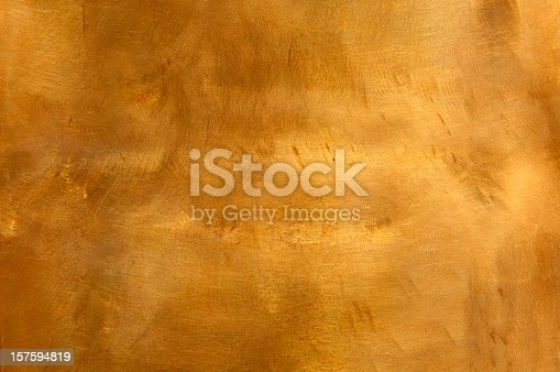 Brushed brown-golden copper or bronze surface, with visible brush strokes. The sheet metal has an appealing cloudy, wavy texture. Horizontal orientation. The image has been shot outdoors during natural day light, full frame and close up. Ideal for backgrounds. The dimensions of the photo are 4223 x 2805 px