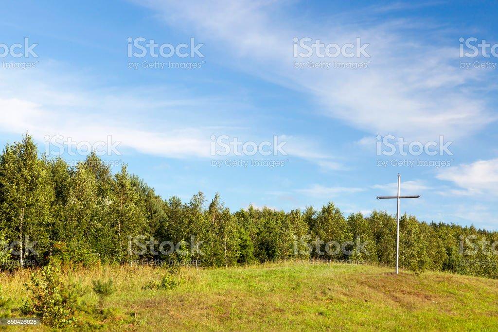metal cross in the wood stock photo