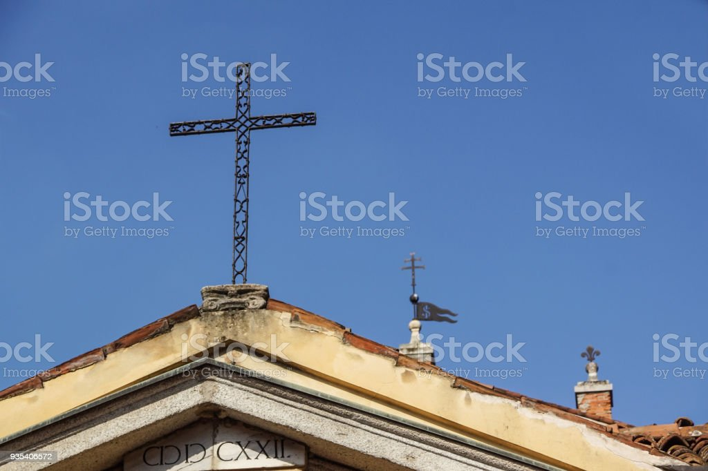 metal cross on a church roof with blue sky as a background stock photo