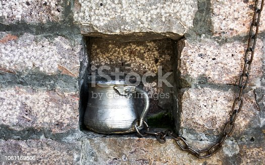 istock Metal cup for drinking water on a chain in the brick wall 1061169806