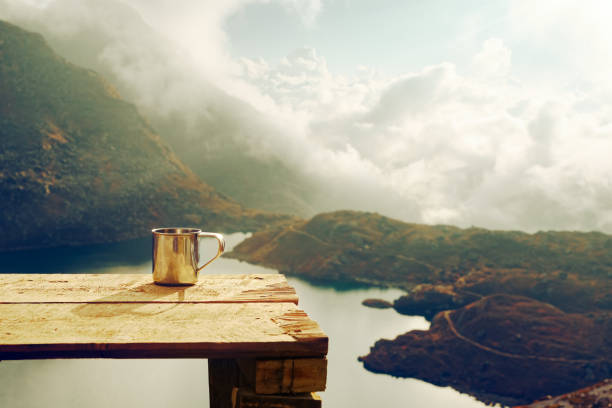 Metal cup on wood table with mountain background at sunrise stock photo
