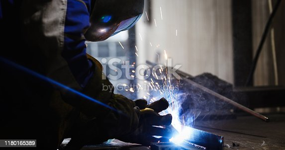 Metal cutting with acetylene torch close-up on low ligth
