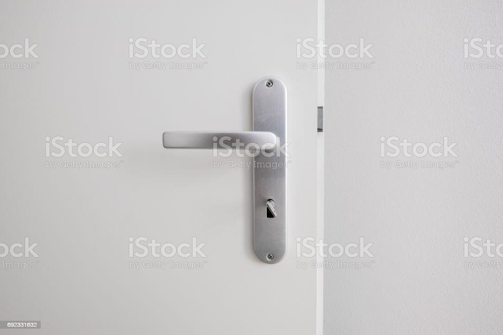 metal door handle with key on white door stock photo