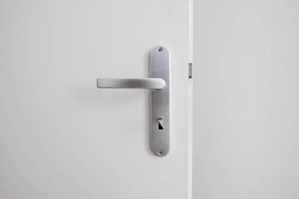maçaneta da porta de metal com chave na porta branca - maçaneta manivela - fotografias e filmes do acervo