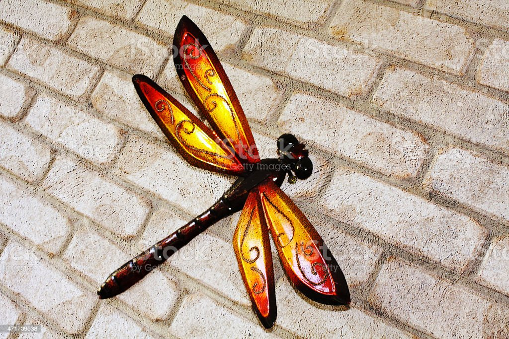 Metal Dragonfly Attached to a Brick Wall stock photo
