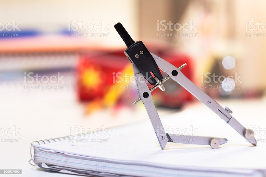 A metal drawing - drafting compass on a notebook. stock photo