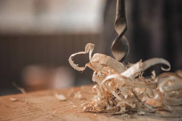 metall bohrer macht ein loch in das holz - tischlerarbeit stock-fotos und bilder