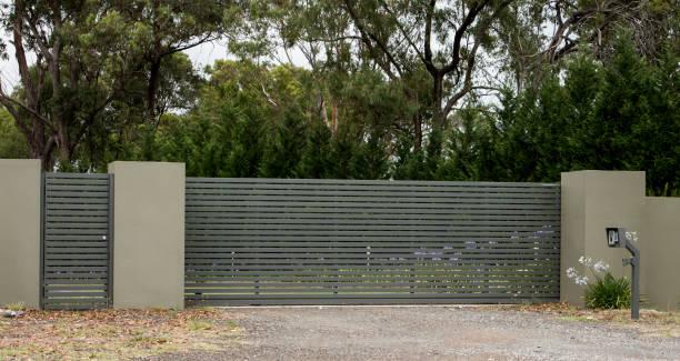 バック グラウンドでユーカリの木と農村プロパティにつながるフェンスをレンガで設定の金属私道の入り口ゲート - 門 ストックフォトと画像