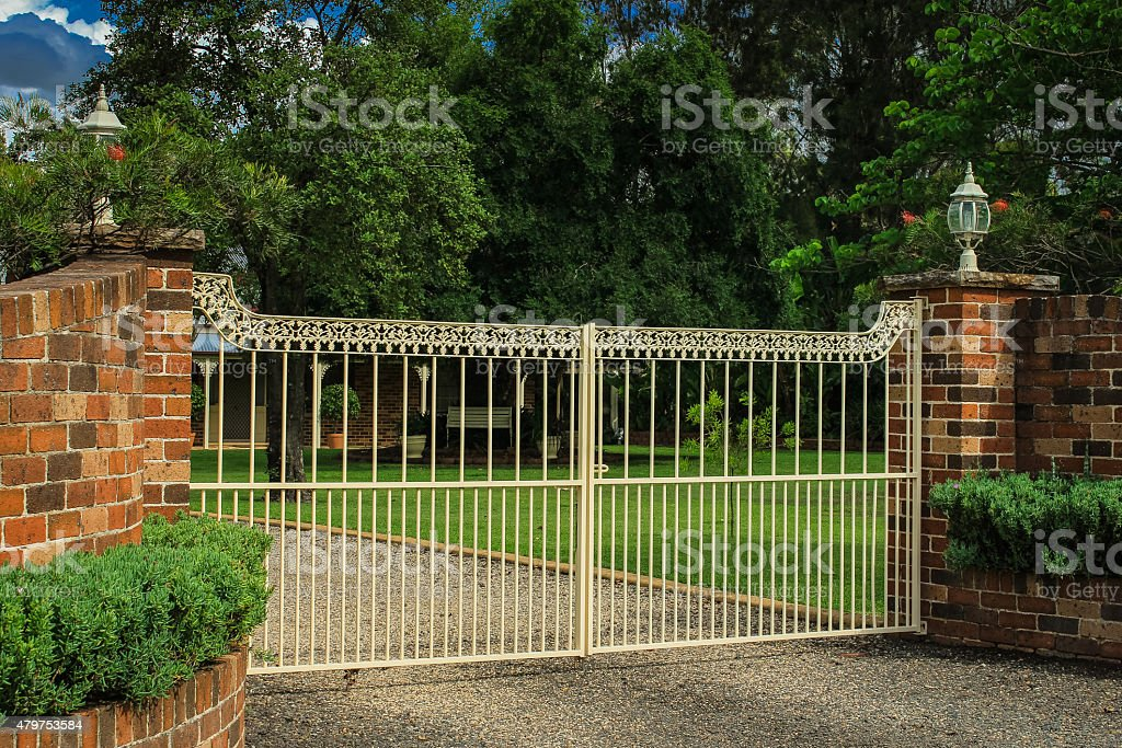 Metal driveway entrance gates set in brick fence stock photo