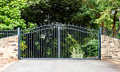 istock Metal driveway property entrance gates set in brick fence with garden trees  in background 1155167055