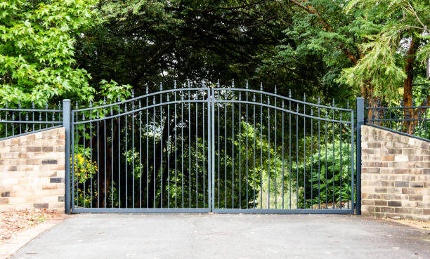 Metal driveway property entrance gates set in brick fence with garden trees  in background Metal driveway property entrance gates set in brick fence with garden trees  in background stone house stock pictures, royalty-free photos & images
