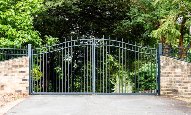 metal driveway property entrance gates set in brick fence with garden trees  in background - portão imagens e fotografias de stock