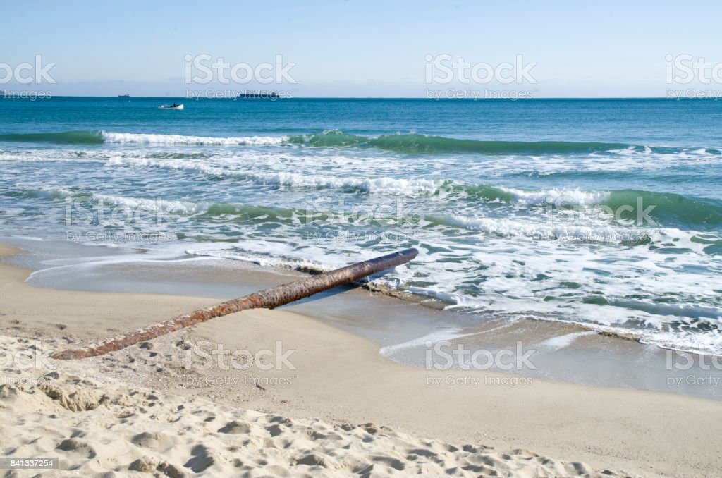 Metal duct pipe on the beach to the sea, outfall stock photo