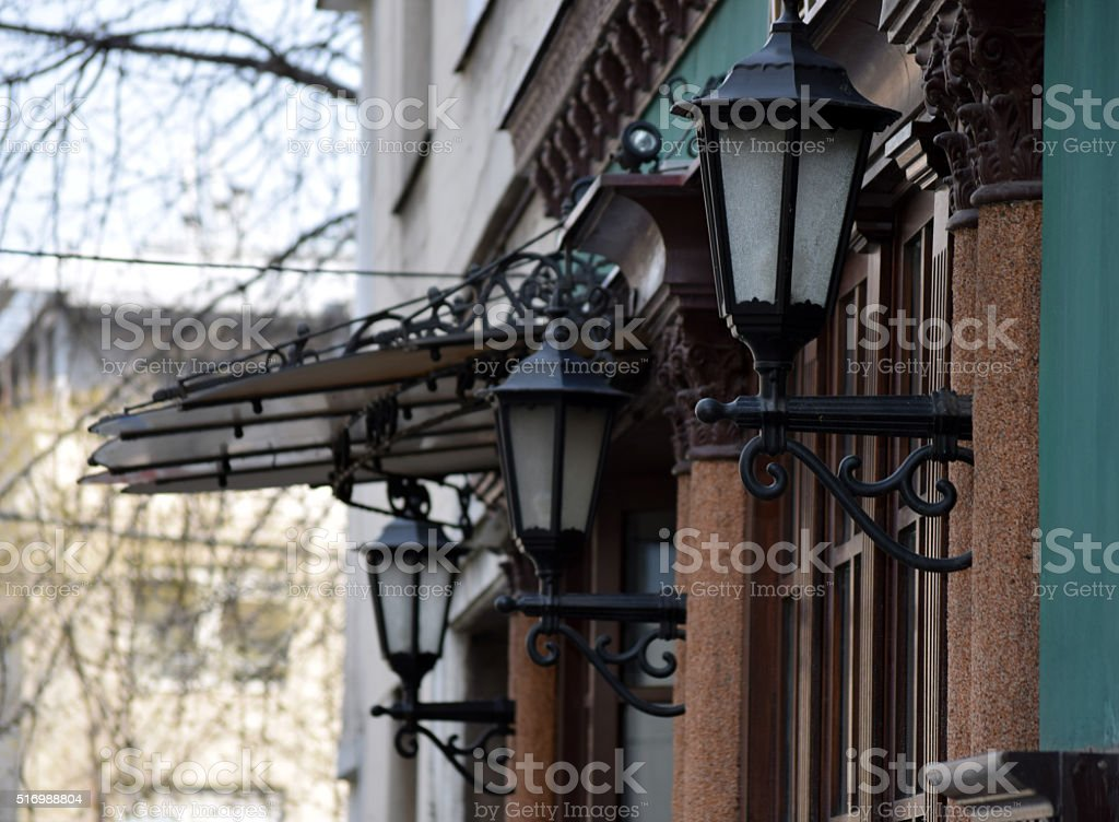 Metal eaves and wall lamps above the wooden door stock photo