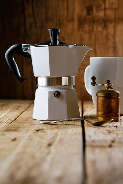 metal espresso maker and coffee grinder on wooden table - argento metallo caffettiera foto e immagini stock