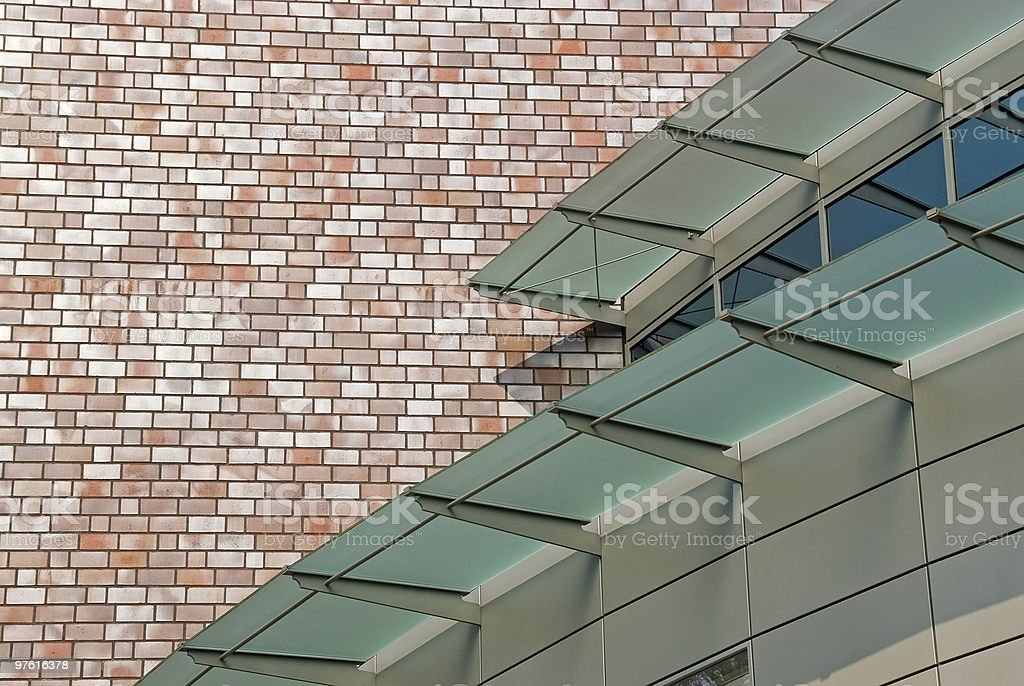 Metal facade with glassy sunprotection in front of brick masonry royalty-free stock photo