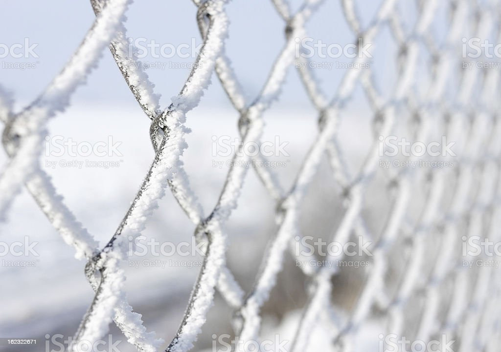 Metal fence covered with frozen snow royalty-free stock photo