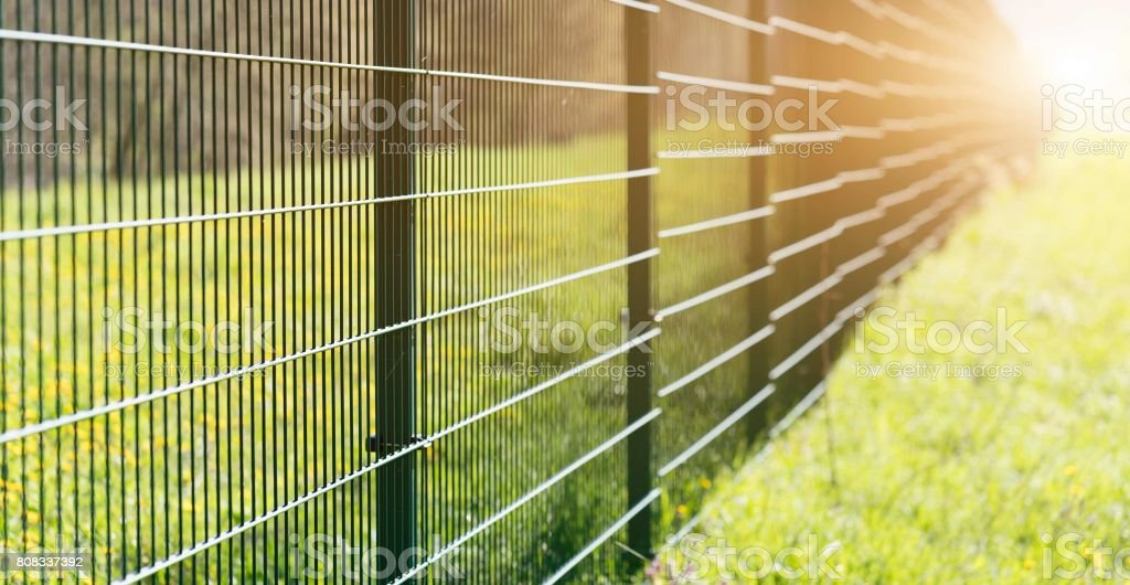 Metal fence leaving in perspective with the sun stock photo