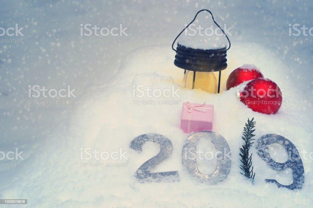 2019 métal figures sur la neige à côté vacances nature morte du nouvel an avec une lampe de poche et des boules rouges. - Photo