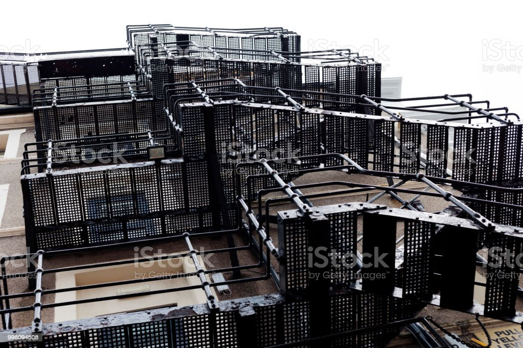 Metal fire escape stairs. Fire escape stairs behind a building. Stairs on the back of the building. Iron staircase to escape. Powdered coated metal fire escape. stock photo